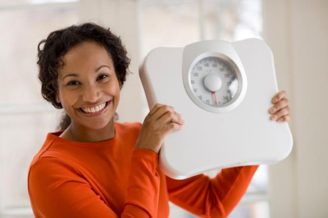 happy woman holding up scale